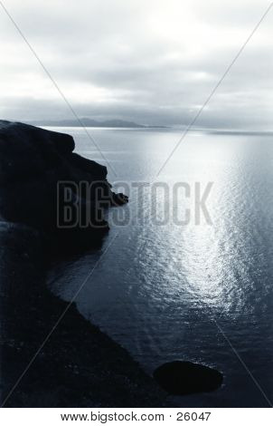 Cliff over the ocean, sun reflecing on the sea, an ocean view, surrounded by islands. computer generated. poster