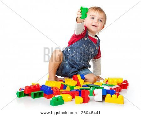 a funny boy is playing with lego. isolated on a white background