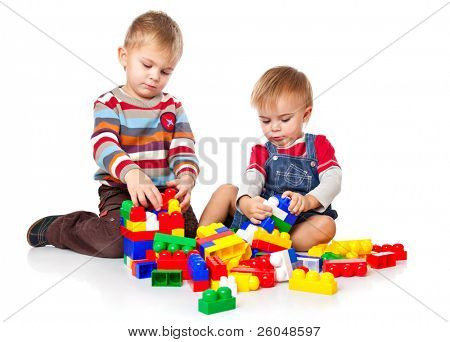 cute boys are playing with the lego. isolated on a white background