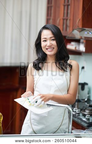 Pretty Asian Woman In White Apron Holding Sponge And Washing Dishes Smiling At Camera In Kitchen