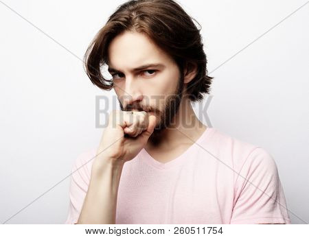 young handsome male with beard, mustache and trendy hairdo, wears casual pink t-shirt, has serious expression as listens to interlocutor poster