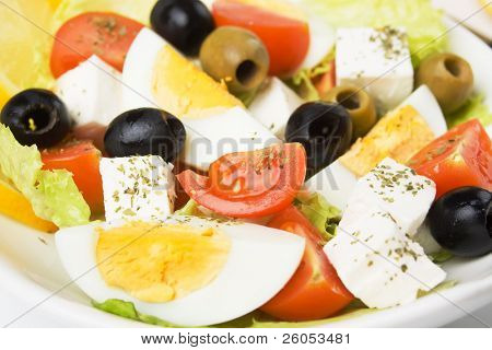 Egg and feta cheese salad with olives, tomato, lettuce