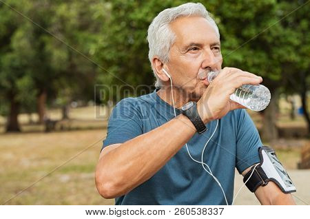 Fit thirsty senior man drinking water before running. Active old man having a break during his jog routine outside. Aged man drinking water while doing fitness in a park.