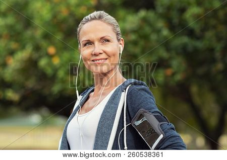 Portrait of a smiling healthy woman with earphones standing in park after running. Proud mature woman looking away after work out. Portrait of satisfied mid woman after fitness exercises.