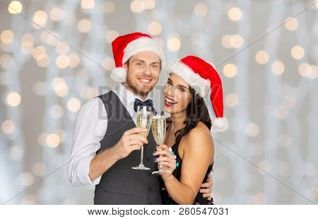 celebration, people and holidays concept - happy couple in santa hats with glasses of non alcoholic champagne at christmas or new year party over festive lights background