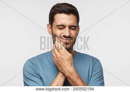 Tooth Ache. Young Man Feeling Pain, Holding His Cheek With Both Hands, Suffering From Bad Toothache,