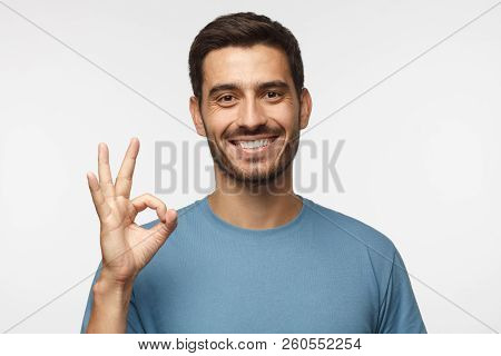Young Man In Blue T-shirt Having Happy Look, Smiling, Gesturing, Showing Ok Sign. Caucasian Male Sho