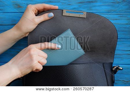 Woman Hand Is Laying A Gray Notebook In A Black Leather Bag