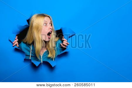 Surprised Woman Looking Through Hole In Paper Wall. Shocked Girl Making Hole In Paper. Pretty Woman