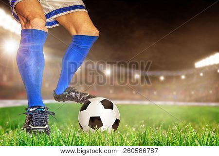 Soccer Player In Action With Football In Brightly Lit Outdoor Stadium. Focus On Foreground And Socce