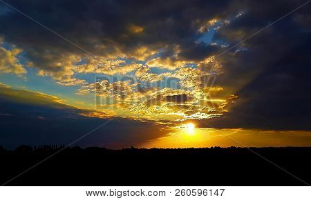 Colorful Sunset In The Ukrainian Steppe, Low Clouds Lush Over The Contrasting Horizon Line