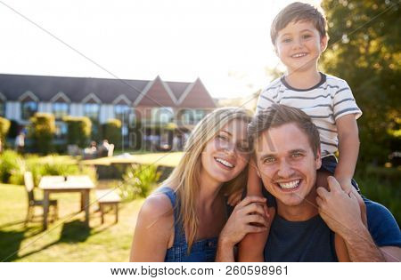 Portrait Of Family With Father Giving Son Ride On Shoulders In Garden Of Summer Pub