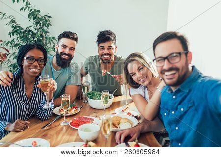 Group Of Happy Young Friends Enjoying Dinner At Home. Group Of Multiethnic Friends Enjoying Dinner P