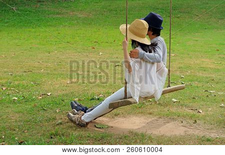 Happy Couple Sitting Side By Side On A Wooden Swing In The Garden