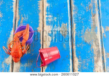 Single Whole Red Boiled Crawfish Near Empty Violet Metal Bucket Beside Red Recumbent Bucket On Old R