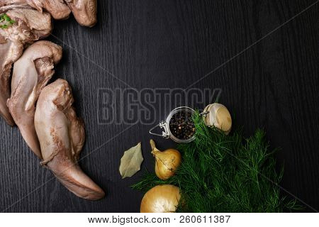 Raw Five Pork Or Beef Tongues With Black Pepper In Glass Jar, Bay Leafs, Onion, Dill On Black Wooden