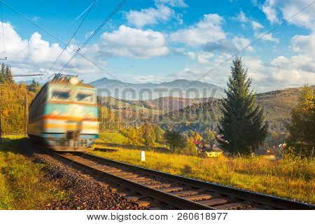 Fast Moving Train In Autumn Mountains. Wonderful Autumn Countryside At Sunrise. Village Down In The