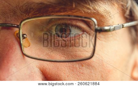 Close-up Of The Male Eye With Glasses. The Concept Of Human Vision, Vision And Care.