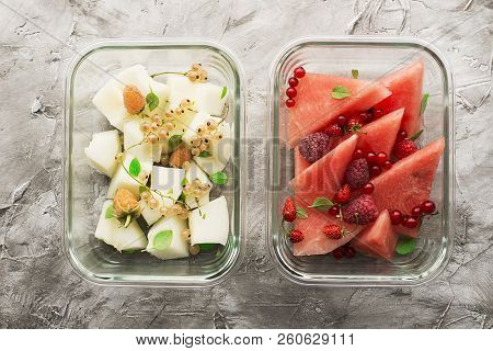 Slices Of Fresh Melon And Watermelon With Fresh Garden Berries In Trendy Glass Containers Of Rectang