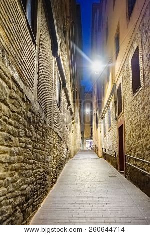 Night Shot Of A Lonely And Narrow Cobblestone Alley With Facades Of Stone Houses Located In The Old