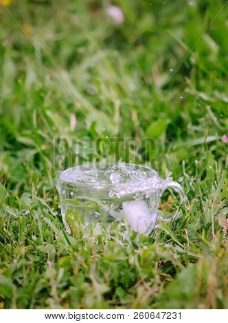 Splash Of Cool Fresh Water With Ice Cubes In The Transparent Glass Cup Outoors In Summer Day.