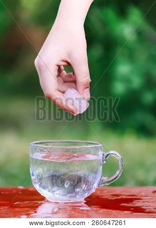 Cool Fresh Water And Ice Cube In Hand Above The Transparent Glass Cup In The Table Outoors In Summer
