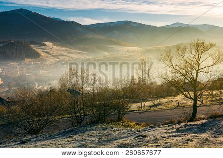 Rural Valley In Autumn At Sunrise. Beautiful Scenery In Mountains. Road Down To Village In Haze And