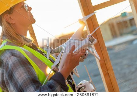 Female Unmanned Aircraft System (UAS) Quadcopter Drone Pilot Holding Drone at Construction Site. poster