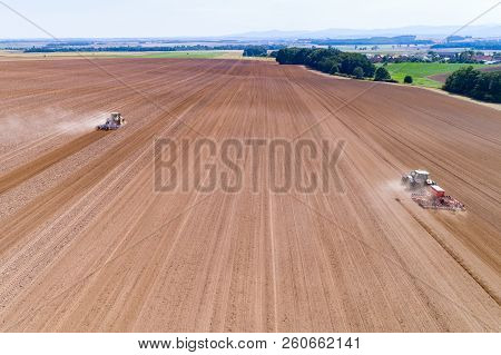 Aerial View On The Tractors Harrownig The Large Brown Field