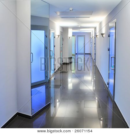 Long, empty corridor in a hospital or office building, with the ceiling lights reflected on the shiny floor.