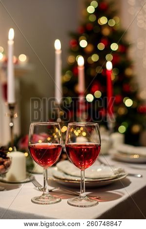 Served Holiday Table With Two Wine Glasses, Blurred New Year Decorations On The Background. Christma
