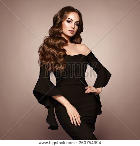 Beautiful Woman In Elegant Black Evening Dress. Brunette Girl With Long Healthy And Shiny Curly Hair