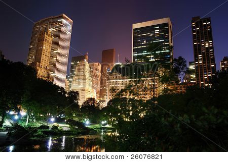 New York City Central Park at night with Manhattan skyscrapers lit with light. poster