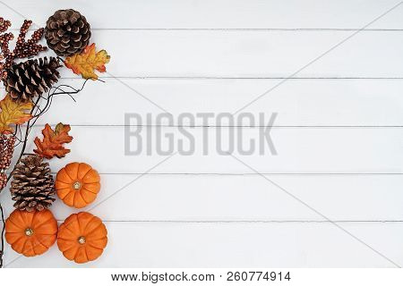 Rustic Fall Background Of Autumn Leaves, Pine Cones And Mini Pumpkins With Free Copy Space For Text