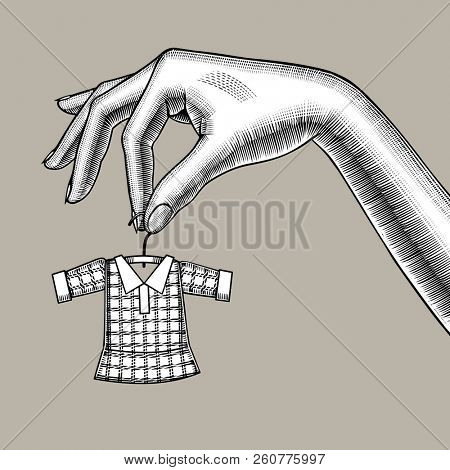 Female hand holding a tiny little dress on hanger. Symbol and metaphor of tailoring. Vintage engraving stylized drawing
