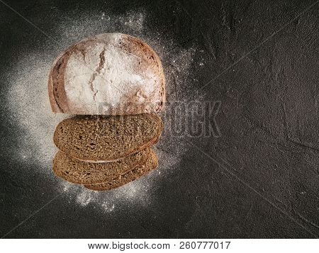 Sliced homemade sourdough rye bread with rye flour on black textured background. Top view or flat-lay. Copy space. Low key poster