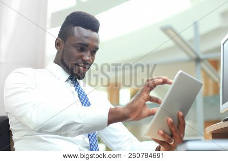 Successful African American Businessman Working On His Touchpad.
