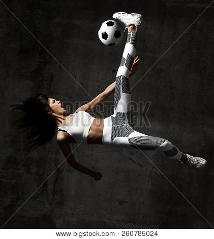 Soccer Woman Player Jumps And Hit The Ball Yelling Screaming On Concrete Loft Wall Background
