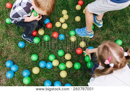 Colored Children's Plastic Toy Balls Spilled In The Grass. Baby Birthday Party Activity