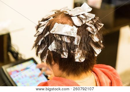 Hair Wrapped With Aluminum Foil  During Chemical Color Hair Dye