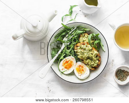 Healthy Breakfast Or Snack - Boiled Egg, Arugula Salad And Avocado Toast On A Light Background, Top