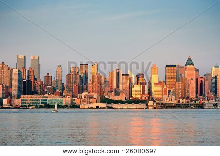 New York City Manhattan midtown skyline at sunset with reflection over skyscraper and river.