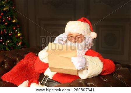 Portrait Of Happy Santa Claus Sitting At His Room At Home Near Christmas Tree And Reading Christmas