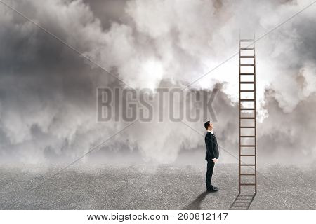 Young Businessman Looking At Ladder On Dull Cloudy Sky Background. Risk And Challenge Concept