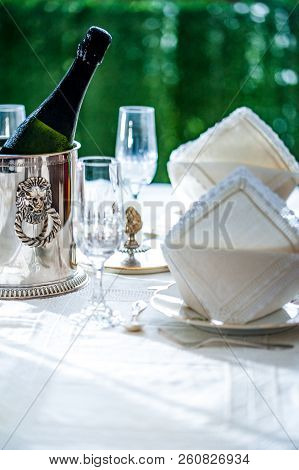 Fine Dinning: White China Dinner Set With Crystal Glassware On A Table With Silver Ice Bucket With A