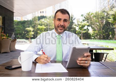 Portrait Of Smiling Mature Executive With Digital Tablet At Cafe. Caucasian Manager Sitting At Table