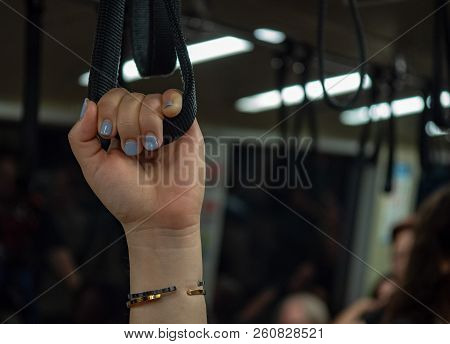 Womans manicured hand holding handrail handle on crowded subway training poster