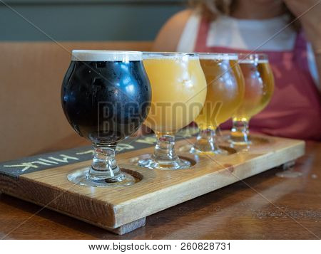 A  Flight Of Stout, Amber, Ipa Beers Sitting On Wooden Paddle