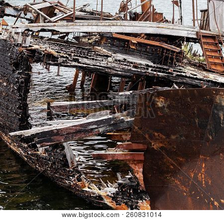 Fragment Of Rotting, Abandoned Ship On The Shore, A Symbol Of Decadence And Degradation