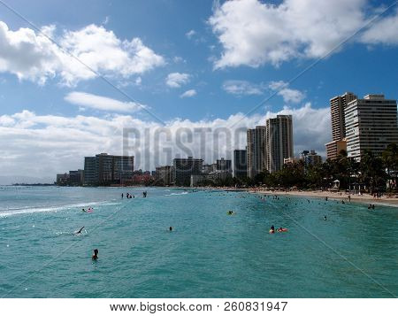 Waikiki - June 7, 2013: People Play In The Protected Water And Hang Out On The Beach In World Famous
